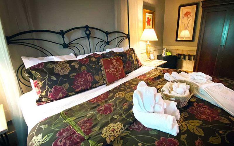 grand gahuti room with king bed, bathrobes, and bath amenities